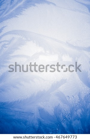 Winter phenomenon - the lacuna. Fractal by patterns of frozen water drops on a frozen window glass. Blue vignetting edging. Good for design backgrounds photo wallpapers displays of electronic devices.