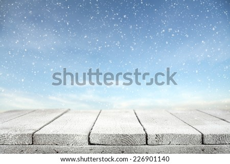 winter photo of blue sky with snow and wooden table  - stock photo