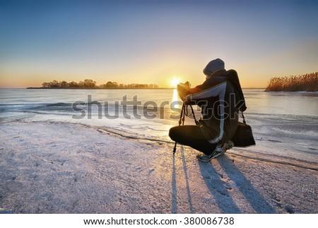 Winter photographer on the ice at sunrise - stock photo