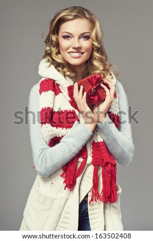 winter picture of beautiful smiling blonde woman wearing a woolen sweater and knitted scarf. Gifts box - stock photo