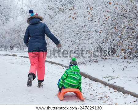 Winter, play, fun - Back view of Mother and her cute little son having fun with sled in winter park