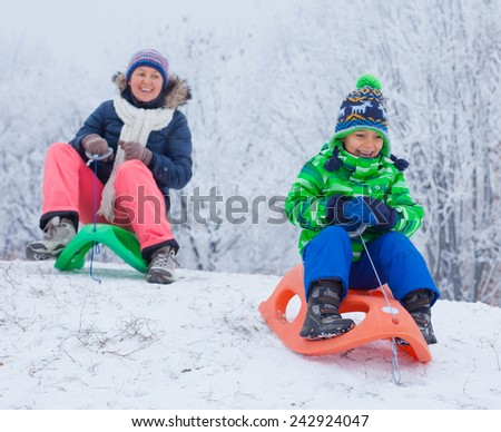 Winter, play, fun - Cute little boy and his mother having fun with sled in winter park