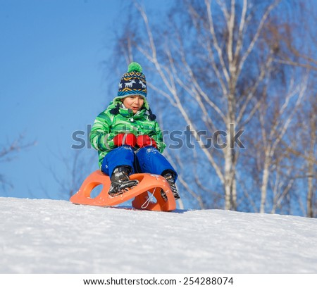 Winter, play, fun - Cute little boy having fun with sled in winter park - stock photo
