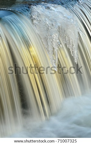 Winter, Portage Creek Cascade framed by icicles and illuminated by golden sunlight, Michigan, USA - stock photo