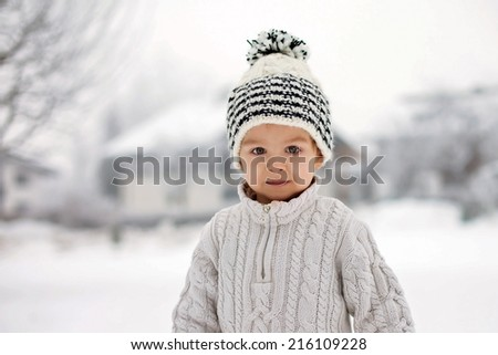 Winter portrait of a boy in the snow - stock photo