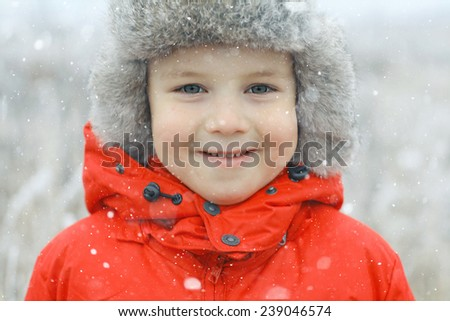 winter portrait of a child in the street, a boy in a cap - stock photo