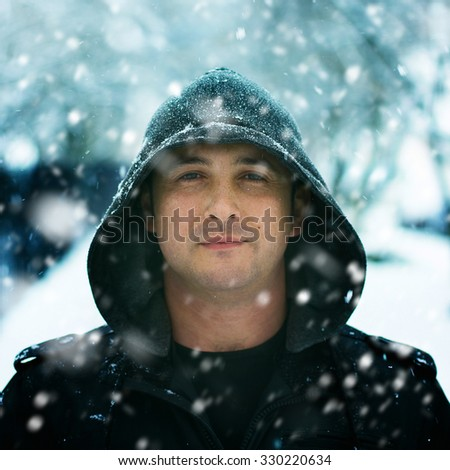 Winter Portrait of a confident calm man wearing hood standing in snowfall. Space for your text above man head. Grain added for best impression. - stock photo