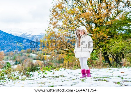 Winter portrait of a cute little girl in a white jacket and pink boots - stock photo