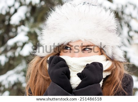Winter portrait of a girl hiding in her scarf.  - stock photo