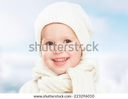 winter portrait of a little happy baby child girl in white hat - stock photo