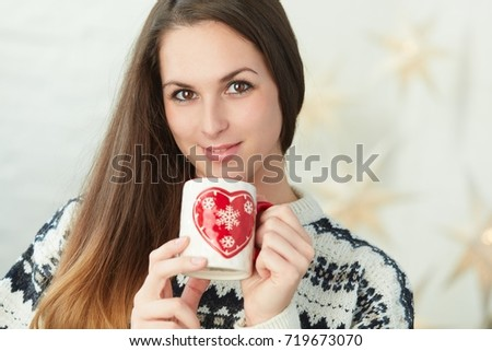 Winter portrait of a pretty young women wearing sweater drinking tea smiling.