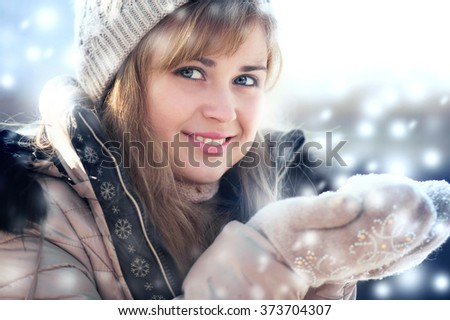 Winter portrait of a woman with snow in hands