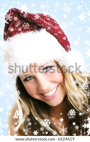 winter portrait of a young smiling woman with a christmas cap and snowflakes
