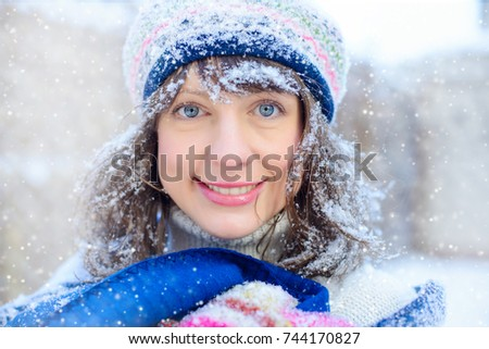 Winter portrait of a young woman. Beauty Joyous Model Girl touching her face skin and laughing, having fun in the winter park. Beautiful young woman outdoors. Enjoying nature, winter and snow sales.