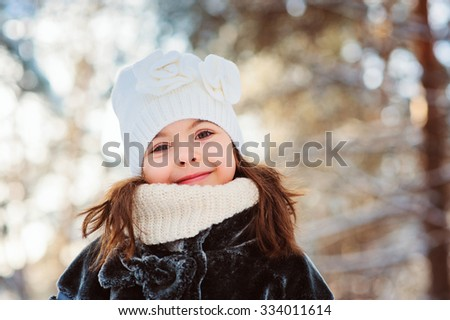 winter portrait of adorable smiling child girl in white hat on the walk in snowy forest. Outdoor activity on holidays. - stock photo