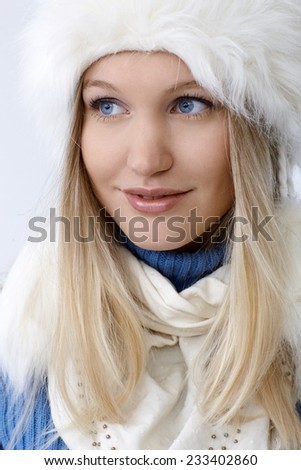 Winter portrait of attractive young blonde woman smiling, looking away. - stock photo