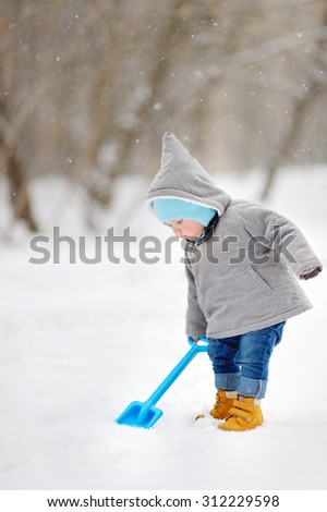 Winter portrait of beautiful toddler boy playing with snow  - stock photo