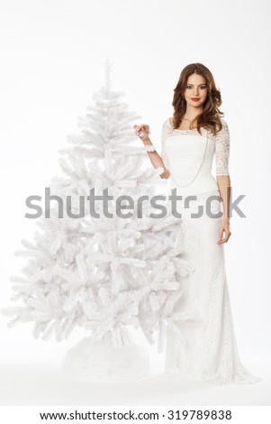 Winter portrait of beautiful woman with a white christmas tree and white christmas bauble. - stock photo