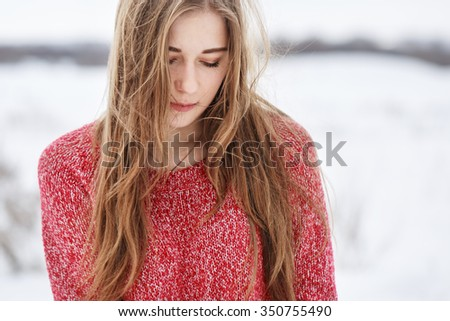 winter portrait of cute attractive beautiful sensitive young blond girl with long hair with red sweater with red lipstick with close eyes on natural background in cloudy field  - stock photo