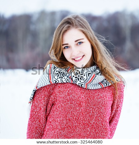 winter portrait of cute pretty young positive smiling girl with beautiful smile with red warm sweater and scarf on natural outdoor background in field - stock photo