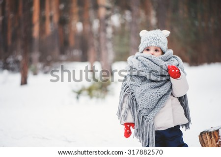 winter portrait of cute toddler girl on the walk in grey knitted hat and oversize scarf - stock photo