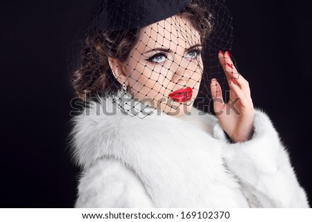 Winter Portrait of elegant retro woman wearing little hat with veil and white fur coat