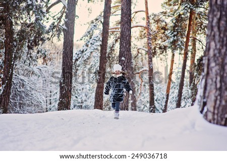 winter portrait of happy child girl running in snowy sunny forest - stock photo