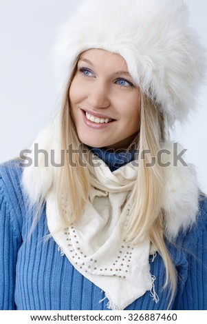 Winter portrait of happy young blonde woman in fur hat, looking away.