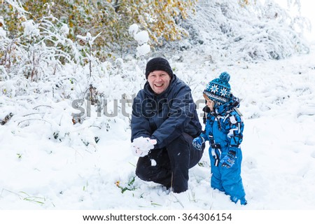 Winter portrait of kid boy and dad in colorful clothes, outdoors during snowfall. Active outoors leisure with children in winter on cold snowy days. Happy man and son having fun with snow in forest - stock photo