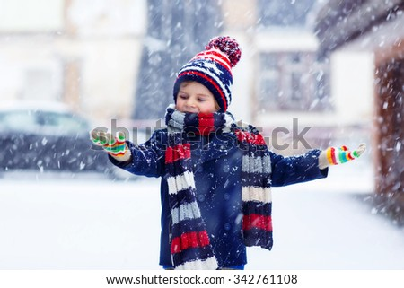 Winter portrait of kid boy in colorful clothes, outdoors during snowfall. Active outdoors leisure with children in winter on cold snowy days. Happy child having fun with snow - stock photo
