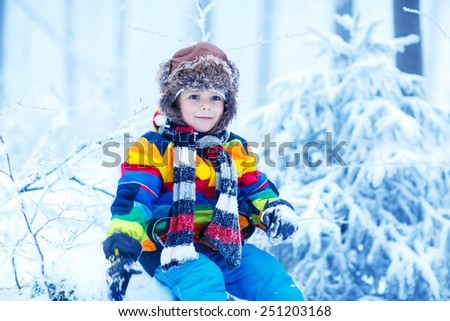Winter portrait of kid boy in colorful winter clothes, outdoors during snowfall. Active outoors leisure with children in winter on cold snowy days - stock photo