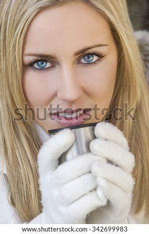 Winter portrait of naturally beautiful woman in her twenties with blond hair and blue eyes wearing gloves and drinking warm drink