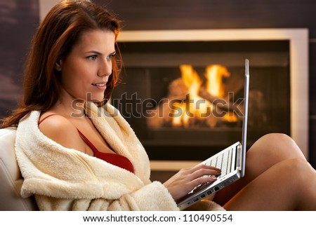 Winter portrait of sexy young woman using laptop computer in bathrobe and red bra in front of fireplace, smiling. - stock photo