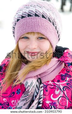 Winter portrait of the beautiful girl in pink woolen cap and scarf - stock photo