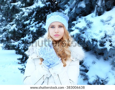 Winter portrait of young beautiful blond woman in her warm clothing in the forest