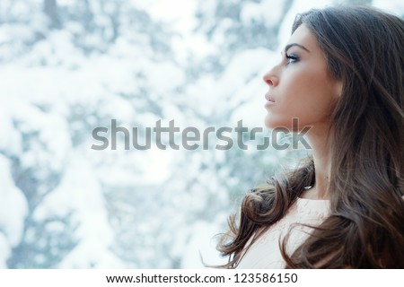 winter portrait of young woman by window - stock photo