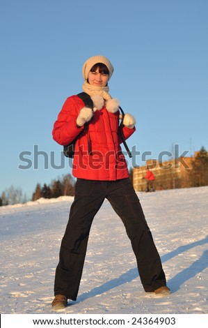 Winter portrait of young woman posing on hill - stock photo