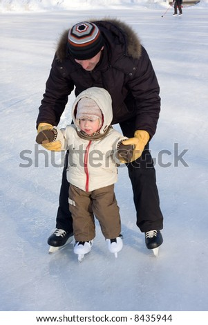Winter recreation. Father and child skating on rink. Focus is on boy's face - stock photo