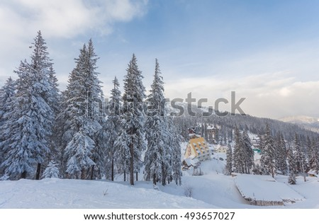Winter resort with slopes for skiing and snowboarding with houses and lifts