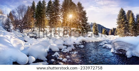 Winter river and forest in the mountains on sunny day - stock photo