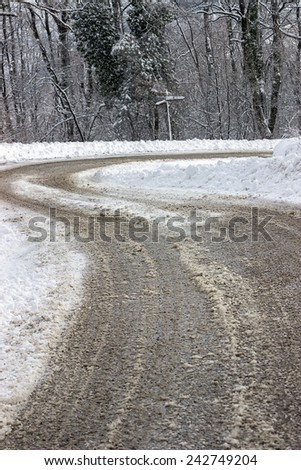 Winter road care, just spread mixture of salt and sand over the ice on a snow covered road. Cleaning a road in winter, sand and salt on road. Selective focus. - stock photo