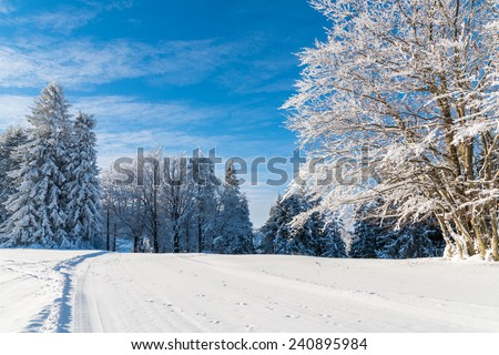 Winter road in Beskid Sadecki Mountains and sunny blue sky, Poland - stock photo