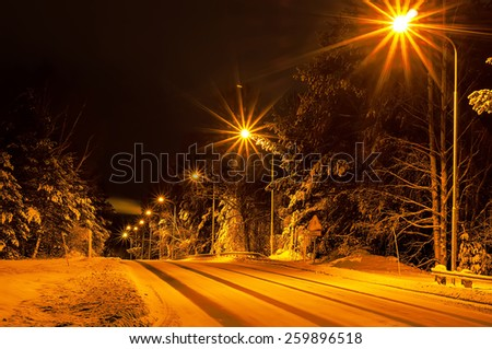 Winter road in the forest with lanterns, natural background - stock photo