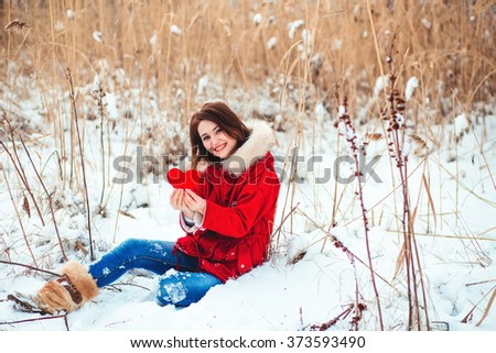 Winter romantic girl holding a red heart - stock photo