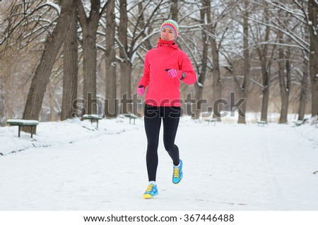 Winter running in park: happy woman runner jogging in snow, outdoor sport and fitness concept  - stock photo