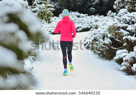 Winter running in park: happy woman runner jogging in snow, outdoor sport and fitness concept