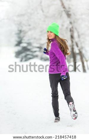 Winter running woman in snowy winter morning. motion, soft daylight - stock photo