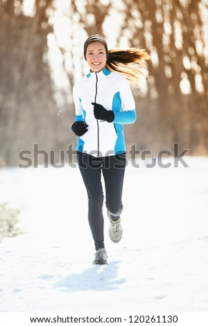 Winter running. Woman runner trail running cold winter forest landscape. Mixed race Asian / Caucasian female cross country running in warm clothes - stock photo
