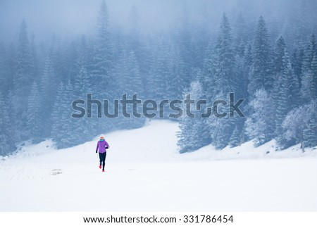 Winter running woman.Sport, fitness, jogging inspiration and motivation. Young happy woman cross country running in mountains on snow, winter day. Female trail runner jogging exercising outdoors. - stock photo