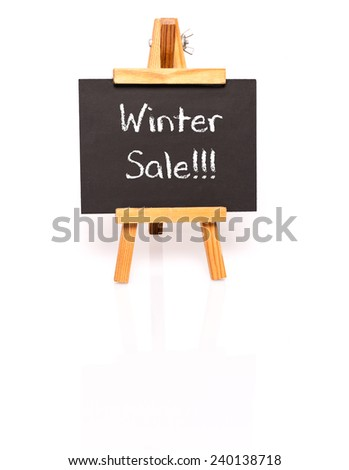 Winter Sale. Blackboard with text and easel. Photo on white background with shadow and reflection. - stock photo